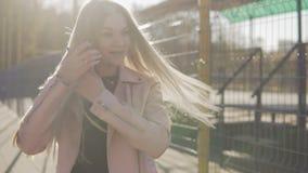 Το όμορφο κορίτσι στο ρόδινο σακάκι γυρίζει γύρω και χαμογελά την εξέταση τη κάμερα υπαίθριο φιλμ μικρού μήκους