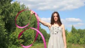Το όμορφο κορίτσι στο φόρεμα στρίβει την κορδέλλα στο δάσος φιλμ μικρού μήκους