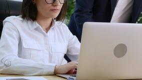 Το όμορφο κορίτσι συσκέπτεται με τα άτομα για το πρόγραμμα για το lap-top στο γραφείο Παρουσιάζει ένα δάχτυλο στην οθόνη ότι εσεί φιλμ μικρού μήκους