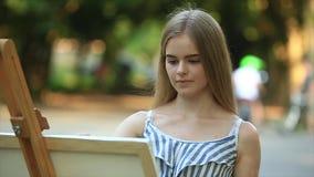 Το όμορφο κορίτσι σύρει μια εικόνα στο πάρκο χρησιμοποιώντας μια παλέτα με τα χρώματα και spatula Easel και καμβάς με μια εικόνα φιλμ μικρού μήκους