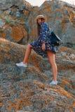 Το όμορφο κορίτσι ταξιδεύει σε ένα καπέλο με ένα όμορφο χαμόγελο στο υπόβαθρο των βουνών και του ουρανού Στοκ φωτογραφία με δικαίωμα ελεύθερης χρήσης