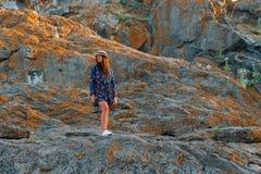Το όμορφο κορίτσι ταξιδεύει σε ένα καπέλο με ένα όμορφο χαμόγελο στο υπόβαθρο των βουνών και του ουρανού Στοκ εικόνες με δικαίωμα ελεύθερης χρήσης