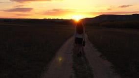 Το όμορφο κορίτσι ταξιδεύει την επαρχία προκλητική επιχειρησιακή γυναίκα που περπατά κατά μήκος μιας εθνικής οδού με έναν χαρτοφύ φιλμ μικρού μήκους