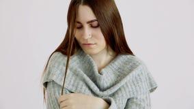 Το όμορφο κορίτσι της ευρωπαϊκής εμφάνισης σε ένα θερμό πουλόβερ θέτει ενάντια σε έναν άσπρο τοίχο συγκινήσεις - calmness και ένα φιλμ μικρού μήκους