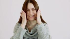 Το όμορφο κορίτσι της ευρωπαϊκής εμφάνισης σε ένα θερμό πουλόβερ θέτει ενάντια σε έναν άσπρο τοίχο συγκινήσεις - χαρά και γέλιο απόθεμα βίντεο