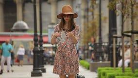 Το όμορφο κορίτσι τουριστών με μια κυλώντας τσάντα αποσκευών πηγαίνει κατά μήκος μιας αλέας και ξετυλίγει έναν χάρτη απόθεμα βίντεο