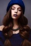 Το όμορφο κορίτσι το χειμώνα έπλεξε το μπλε χρώμα καπέλων με ένα περιδέραιο γύρω από το λαιμό των μαργαριταριών Νέο πρότυπο με τη στοκ φωτογραφίες