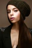 Το όμορφο κορίτσι το χειμώνα πλέκει το καπέλο και το χακί σακάκι Νέο πρότυπο με την ευγενή σύνθεση και τα χρωματισμένα βέλη στοκ φωτογραφία με δικαίωμα ελεύθερης χρήσης