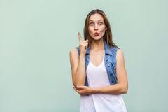 Το όμορφο κορίτσι φακίδων πήρε την ιδέα και έβαλε το δάχτυλό της επάνω Στοκ Εικόνα