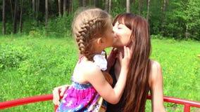 Το όμορφο κορίτσι φιλά τη μητέρα της στο πράσινο θερινό πάρκο φιλμ μικρού μήκους