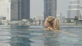 Το όμορφο κορίτσι χαλαρώνει σε μια λίμνη απείρου φιλμ μικρού μήκους