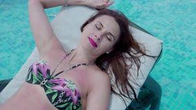 Το όμορφο κορίτσι χαλαρώνει στην υπαίθρια πισίνα 4K απόθεμα βίντεο