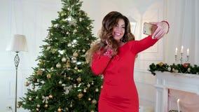 Το όμορφο κορίτσι Χριστουγέννων γιορτάζει το νέο έτος κοντά στο χριστουγεννιάτικο δέντρο, που φωτογραφίζεται με κινητό τηλέφωνο,  απόθεμα βίντεο
