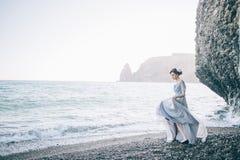 Το όμορφο κορίτσι brunette σε ένα μακρύ γκρίζο φόρεμα φιαγμένο από Tulle είναι στην προκυμαία, κοντά στους υψηλούς απότομους βράχ Στοκ φωτογραφία με δικαίωμα ελεύθερης χρήσης