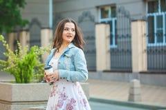 Το όμορφο κορίτσι brunette σε ένα σακάκι τζιν περπατά γύρω από την πόλη με τον καφέ στα χέρια στοκ φωτογραφίες