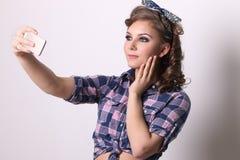 Το όμορφο κορίτσι Pinup στο ελεγμένο πουκάμισο κάνει selfie Στοκ εικόνα με δικαίωμα ελεύθερης χρήσης