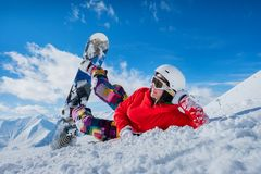 Το όμορφο κορίτσι snowboarder βρίσκεται στο χιόνι κοιτάζοντας στην πλευρά Στοκ Φωτογραφίες