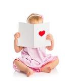 Το όμορφο κοριτσάκι με τη χαριτωμένη κάρτα βαλεντίνων με ένα κόκκινο ακούει Στοκ Φωτογραφία