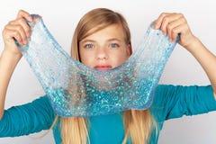 Το όμορφο κράτημα νέων κοριτσιών ακτινοβολεί slime μπροστά από το πρόσωπό της στοκ φωτογραφία με δικαίωμα ελεύθερης χρήσης