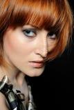 Το όμορφο κόκκινο η γυναίκα με τη μόδα hairstyle Στοκ Εικόνα