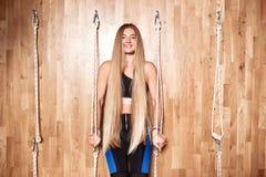 Το όμορφο λεπτό κορίτσι με τα πολύ μακριά ξανθά μαλλιά που ντύνονται sportswear στέκεται δίπλα στον ειδικό εξοπλισμό σχοινιών μέσ στοκ φωτογραφία
