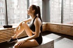 Το όμορφο λεπτό κορίτσι που ντύνεται στη μαύρα αθλητικά κορυφή και τα σορτς κάθεται σε ένα ξύλινο κιβώτιο στο φως του ήλιου στο μ στοκ φωτογραφίες με δικαίωμα ελεύθερης χρήσης