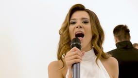 Το όμορφο λευκό κορίτσι τραγουδά Μια ομάδα επαγγελματικών χορευτών αποδίδει μαζί με το απόθεμα βίντεο