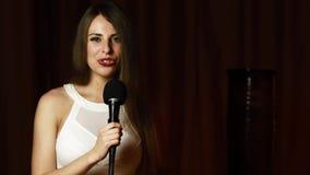 Το όμορφο μακρυμάλλες κορίτσι κρατά mic, εξετάζει τη κάμερα και τραγουδά με το χαμόγελο απόθεμα βίντεο