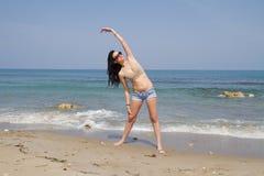Το όμορφο μακρυμάλλες brunette στη beachwear άσκηση είναι στοκ εικόνες με δικαίωμα ελεύθερης χρήσης
