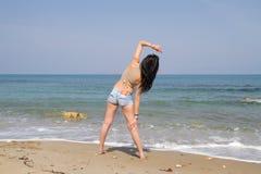 Το όμορφο μακρυμάλλες brunette στη beachwear άσκηση είναι στοκ φωτογραφία με δικαίωμα ελεύθερης χρήσης