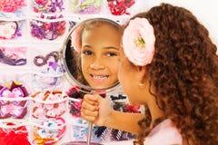 Το όμορφο μικρό αφρικανικό κορίτσι απεικονίζει στον καθρέφτη Στοκ Εικόνες