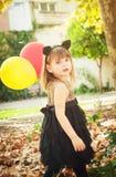 Το όμορφο μικρό κορίτσι έντυσε ως γάτα με τα μπαλόνια στα χέρια Το γλυκό χαμόγελο, μια προσφορά κοιτάζει στοκ φωτογραφία
