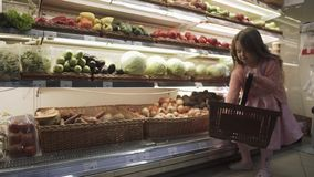 Το όμορφο μικρό κορίτσι βάζει τα λαχανικά και τα φρούτα σε ένα καλάθι στη λεωφόρο φιλμ μικρού μήκους