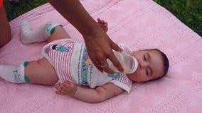 Το όμορφο μικρό κορίτσι βρίσκεται σε ένα ρόδινο κάλυμμα στον κήπο στη χλόη Το Mom δίνει το παιδί πίνει το τσάι από ένα μπουκάλι φιλμ μικρού μήκους
