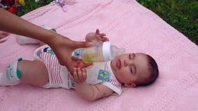 Το όμορφο μικρό κορίτσι βρίσκεται σε ένα ρόδινο κάλυμμα στον κήπο στη χλόη Το Mom δίνει το παιδί πίνει το τσάι από ένα μπουκάλι απόθεμα βίντεο