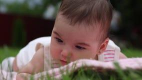 Το όμορφο μικρό κορίτσι βρίσκεται σε ένα ρόδινο κάλυμμα στον κήπο στη χλόη στο στομάχι φιλμ μικρού μήκους