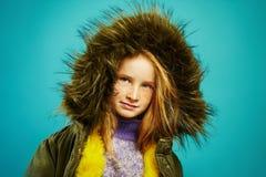 Το όμορφο μικρό κορίτσι είναι ντυμένο στο πράσινο χειμερινό σακάκι με την κουκούλα στο μπλε υπόβαθρο στοκ εικόνα με δικαίωμα ελεύθερης χρήσης