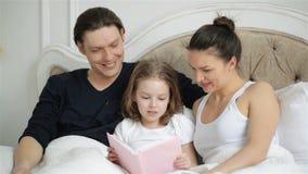 Το όμορφο μικρό κορίτσι διαβάζει μεγαλοφώνως το βιβλίο στο κρεβάτι με τους γονείς της Ο όμορφος πατέρας φιλά έξυπνό του απόθεμα βίντεο