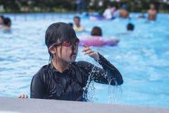 Το όμορφο μικρό κορίτσι κολυμπά στη λίμνη, χαριτωμένο μικρό κορίτσι στη λίμνη στην ηλιόλουστη ημέρα στοκ εικόνες