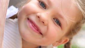 Το όμορφο μικρό κορίτσι κρυφοκοιτάζει έξω από το σωλήνα στην παιδική χαρά στη θερινή ημέρα απόθεμα βίντεο