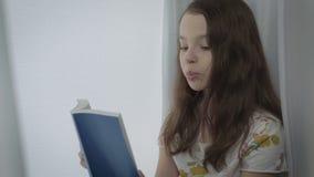 Το όμορφο μικρό κορίτσι μαθαίνει ένα ποίημα από το παράθυρο φιλμ μικρού μήκους