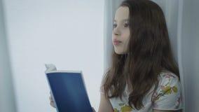 Το όμορφο μικρό κορίτσι μαθαίνει ένα ποίημα από το παράθυρο απόθεμα βίντεο