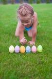 Το όμορφο μικρό κορίτσι μετρά τα αυγά Πάσχας σε πράσινο Στοκ εικόνες με δικαίωμα ελεύθερης χρήσης