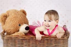 Το όμορφο μικρό κορίτσι με μεγάλο teddy αντέχει στο ψάθινο καλάθι στοκ εικόνα