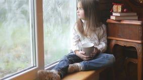 Το όμορφο μικρό κορίτσι με μια κούπα του καυτού τσαγιού κάθεται από το παράθυρο απόθεμα βίντεο