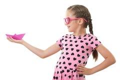 Το όμορφο μικρό κορίτσι με το πορτρέτο στούντιο σκαφών εγγράφου, έντυσε στο ροζ με τις μορφές καρδιών, άσπρο υπόβαθρο Στοκ εικόνες με δικαίωμα ελεύθερης χρήσης