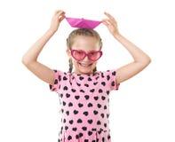 Το όμορφο μικρό κορίτσι με το πορτρέτο στούντιο σκαφών εγγράφου, έντυσε στο ροζ με τις μορφές καρδιών, άσπρο υπόβαθρο Στοκ Εικόνες