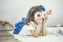 Το όμορφο μικρό κορίτσι με τα πιάτα, τα γλυκά και τις κούκλες παιχνιδιών είναι playi Στοκ Φωτογραφίες