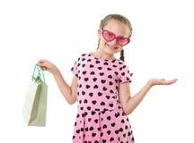 Το όμορφο μικρό κορίτσι με την τσάντα αγορών, πορτρέτο στούντιο, έντυσε στο ροζ με τις μορφές καρδιών, άσπρο υπόβαθρο Στοκ φωτογραφία με δικαίωμα ελεύθερης χρήσης