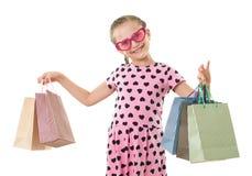 Το όμορφο μικρό κορίτσι με την τσάντα αγορών, πορτρέτο στούντιο, έντυσε στο ροζ με τις μορφές καρδιών, άσπρο υπόβαθρο Στοκ Φωτογραφίες